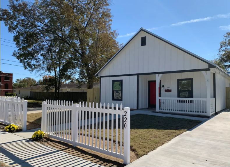 The Farmhouse in Pawhuska - white home with country porch and a red front door behind a white picket fence