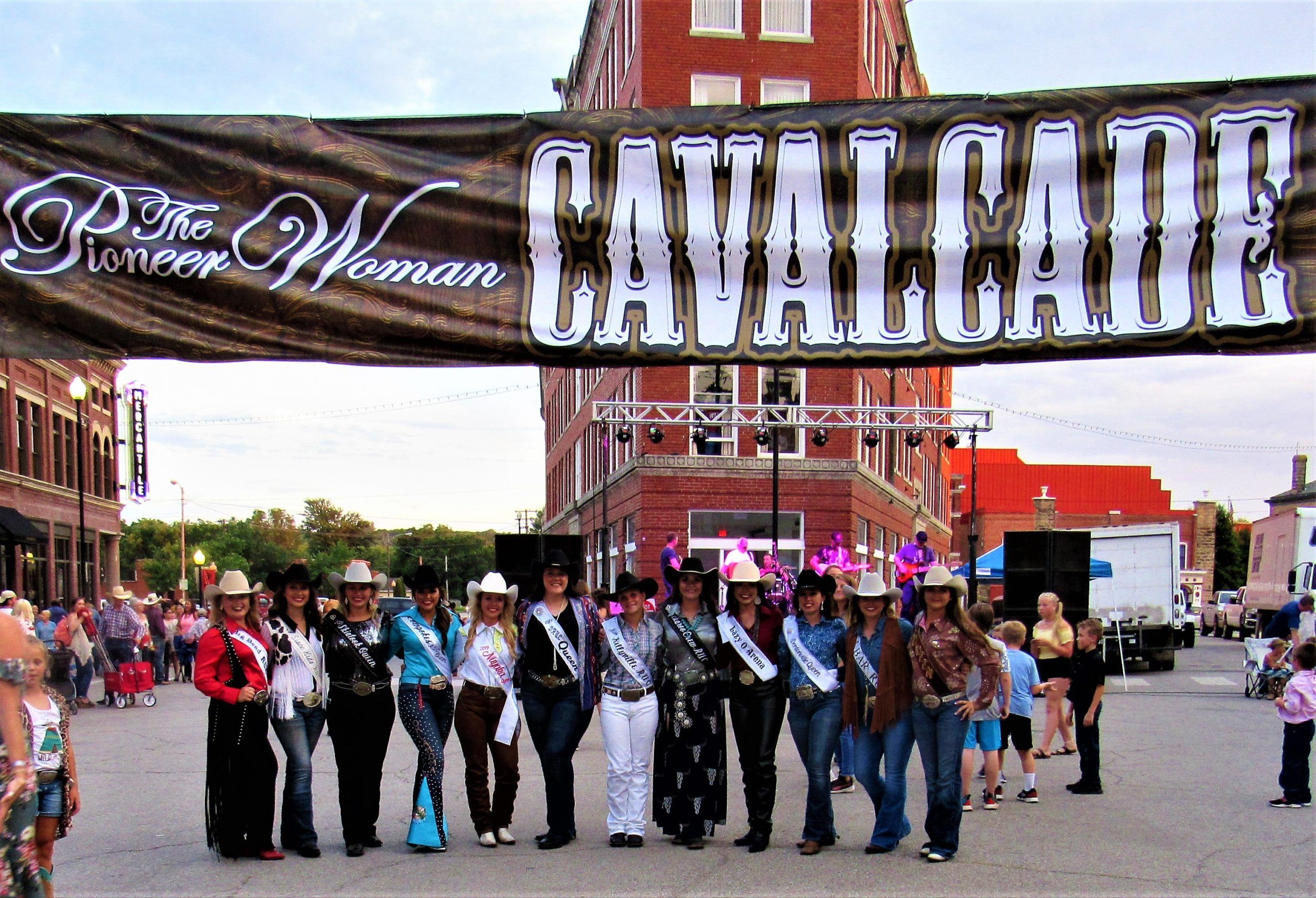 Cavalcade Rodeo banner hanging across the streets of Pawhuska with rodeo queens in cowboy hats under it on the streets